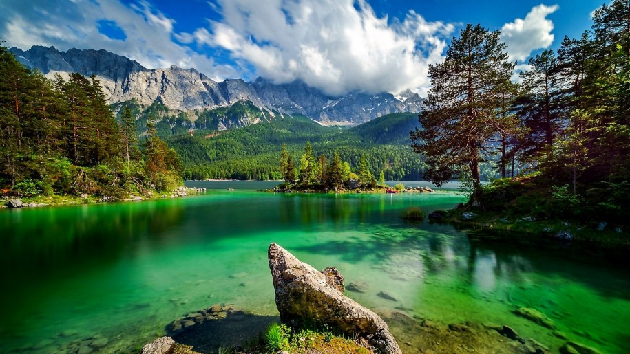 Lake-with-turquoise-green-water-rock-island-rocky-mountains-pine-forest-sky-with-white-clouds-Summer-HD-Wallpaper-915x515